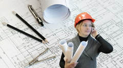Woman engineer with blueprints talking with cellphone, drawings background Stock Footage