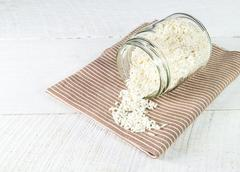 Rice grain in glass bottles on brown cloth Stock Photos