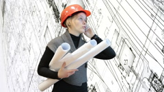 Woman architect talking by cellphone and holding blueprints Stock Footage