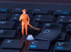 Miniature worker with broom working on keyboard Stock Photos