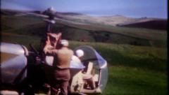 1326 - crop duster helicopter flying over farmers field-vintage film home movie  Stock Footage