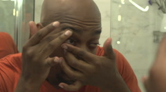 A black man, in reflection, inserts a contact lens Stock Footage