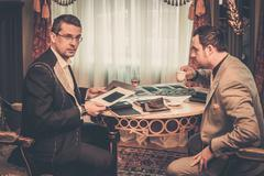 Stock Photo of tailor and client choosing cloth and buttons for custom made suit