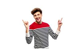 Stock Photo of laughing casual man pointing upwards over white background