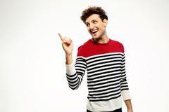 Happy casual man pointing upwards over gray background Stock Photos