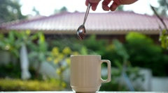 Male Hand Stirs Steaming Cup of Tea Outdoors. Slow Motion. Stock Footage