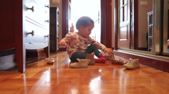 Baby girl trying put on shoes sitting over wooden floor Stock Footage