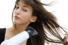 Portrait of a young woman using a hair drier - stock photo