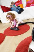2 children at home, little girl vacuuming, little boy sitting on a sofa Stock Photos