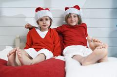 2 boys on bed, disguised as Santa Claus Stock Photos