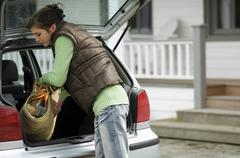 Young woman taking a shopping basket out of a car trunk Stock Photos