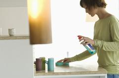 Young woman cleaning kitchen work-top Stock Photos