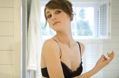 Portrait of a woman in black bra spraying perfume Stock Photos