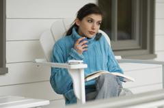 Young woman reading, sitting on a chair, outdoors Stock Photos