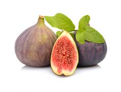 three sliced figs lengthwise in half with spearmint, isolated on white backgr - stock photo