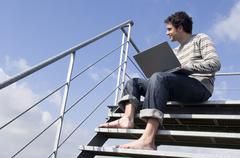 Man sitting on stairs, using laptop, outdoors, low angle Stock Photos