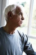 Thinking senior man looking through a window Stock Photos
