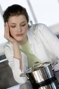 Young woman watching over saucepan on vitroceramic hob Stock Photos