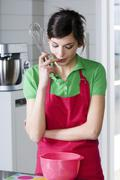 Young thinking woman in the kitchen, holding a whisk Stock Photos