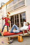 Young woman with cleaning accessories shouting at man lying on a deck chair - stock photo