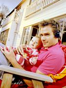 Young man with headphones holding baby, lying on a deck chair - stock photo