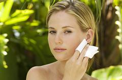 Portrait of a young woman using a cleansing cotton on her face, outdoors Stock Photos