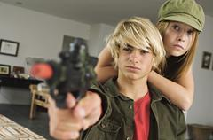Teenage girl and boy aiming fake handgun Stock Photos