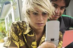 2 teenage boys using mobile phone - stock photo