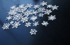 white paper snowflakes on dark blue background - stock photo