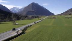 Aerial, slow motion - Cars driving on a road to Julian Alps Stock Footage