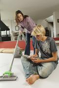 Mother vacuuming and speaking to his son, sitting on floor, indoors Stock Photos