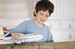 Little boy playing with model aeroplane - stock photo