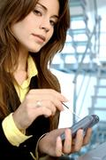Businesswoman operating mobile phone with stylus Stock Photos