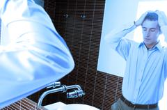 Reflection of mature man standing in front of mirror in washroom Stock Photos
