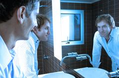 Men looking at mirror in washroom, smiling Stock Photos