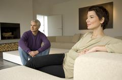 Mature man and a mid adult woman sitting in a living room Stock Photos