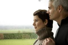 Mature man and a mid adult woman looking out through a window Stock Photos