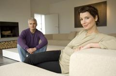 Portrait of a mid adult woman and a mature man sitting in a living room Stock Photos