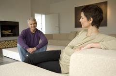 Mid adult woman and a mature man sitting in a living room Stock Photos