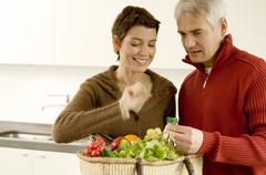 Mature man holding a bunch of grapes with a mid adult woman standing beside him Stock Photos