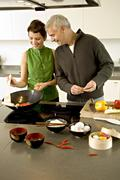 Mature man and a mid adult woman preparing food in the kitchen Stock Photos