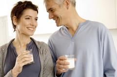 Mature man and a mid adult woman holding glasses of milk Stock Photos