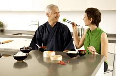 Mid adult woman feeding food to a mature man in the kitchen Stock Photos
