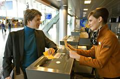 Businessman with a female check-in attendant at an airport check-in counter Stock Photos