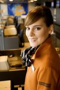 Portrait of a female airline check-in attendant smiling at an airport check-in - stock photo