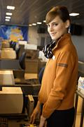 Portrait of a female airline check-in attendant at an airport check-in counter - stock photo