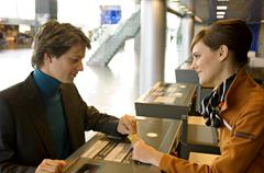 Businessman with a female check-in attendant at an airport check-in counter - stock photo