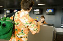 Female airline check-in attendant giving a passport and boarding pass to a Stock Photos