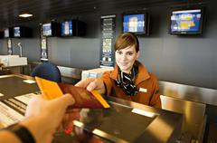 Female airline check-in attendant giving a passport and boarding pass to a - stock photo