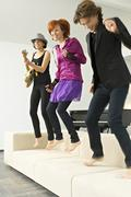 Two young women and a teenage boy dancing on a couch Stock Photos